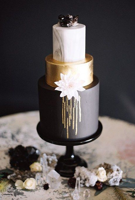 a chic wedding cake with a black, gold and marble layer topped with a geode for an art deco winter wedding