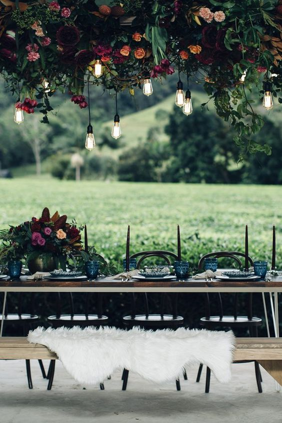 a dark industrial wedding tablescape with bulbs, moody florals, black candles and faux fur