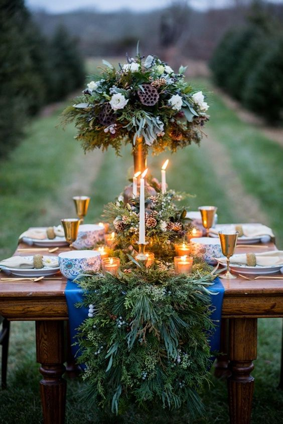 a rustic evergreen table runner with berries and pinecones and lots of candles bring winter spirit