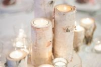 14 birch candle holders placed on a birch slice and surrounded with additional candles