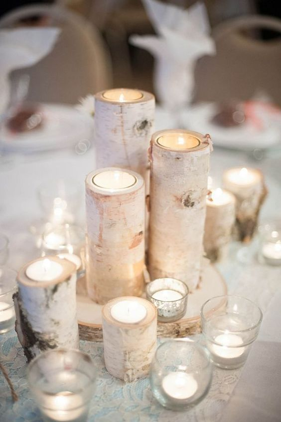 birch candle holders placed on a birch slice and surrounded with additional candles