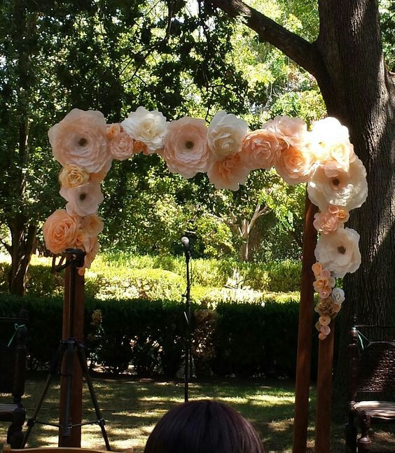 peachy and blush paper flowers for decorating a wedding arch is a simple and budget-friendly idea