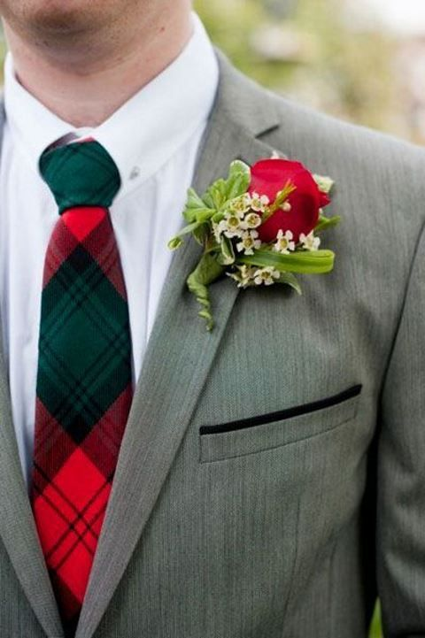the groom in a grey suit with a traditional christmas-inspired tie and a red boutonniere