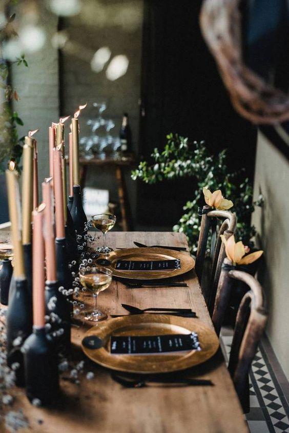 a dark winter tablescape mit schwarzen Flaschen zu halten Kerzen, gold Ladegeräte und schwarz Menüs