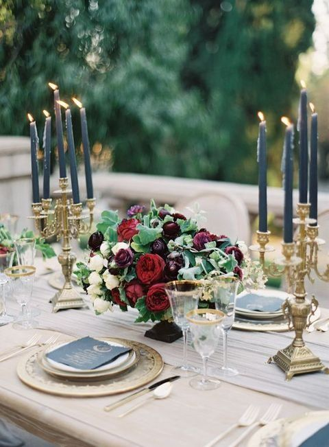 a luxurious table setting with gold candle holders, chargers, gold rim glasses and dark florals