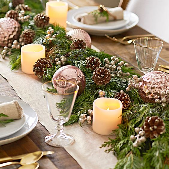 an evergreen table runner with berries, snowy pinecones, copper ornaments and candles