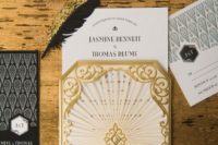 15 black, gold and white wedding invitations with black and gold feathers