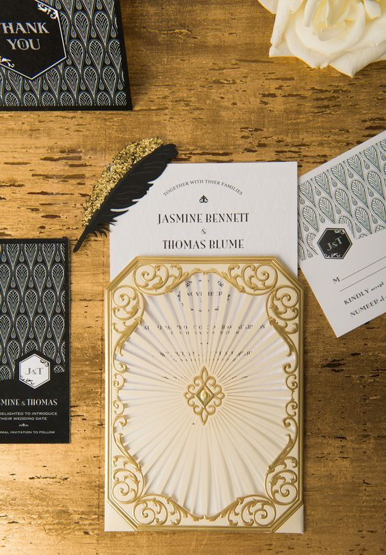 black, gold and white wedding invitations with black and gold feathers