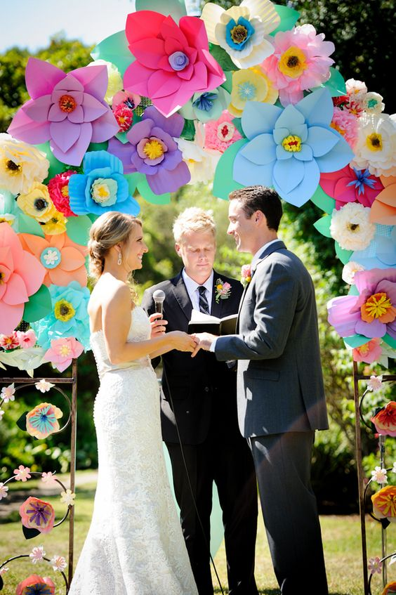 various colorful paper flowers on the wedding arch create a bold and cheerful ambience