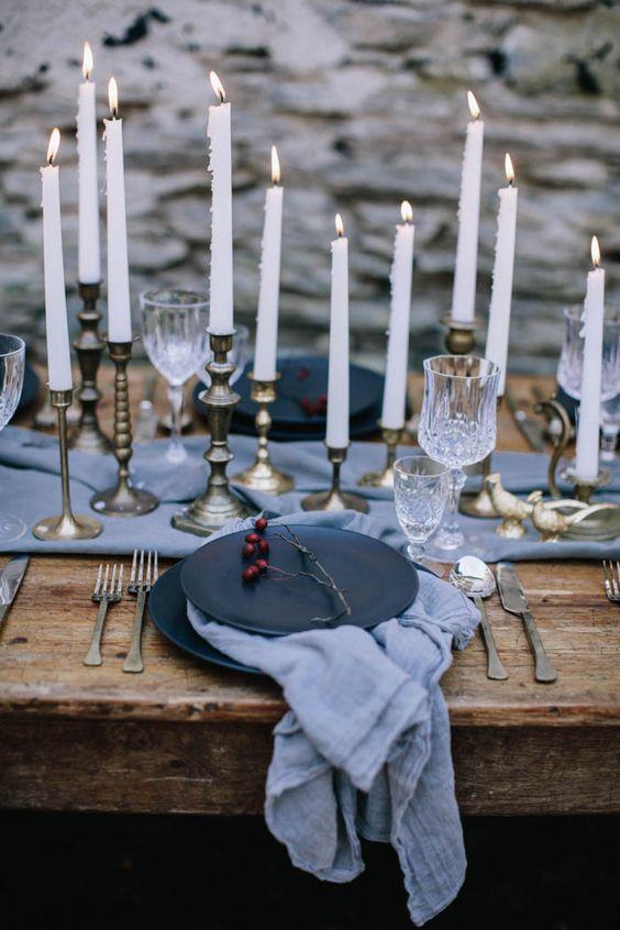 moody Küsten-tablescape mit einem hellblauen Tischläufer und Servietten, schwarz, Teller und Kerzen