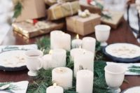 16 a simple evergreen runner and pillar candles on it for a modern winter wedding