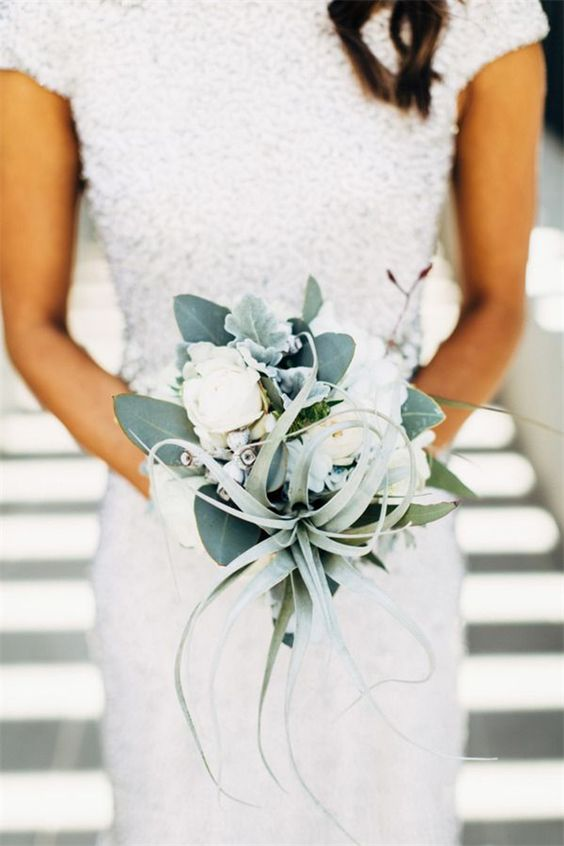 an air plant, pale leaves and some white blooms wedding bouquet for a non-traditional bride