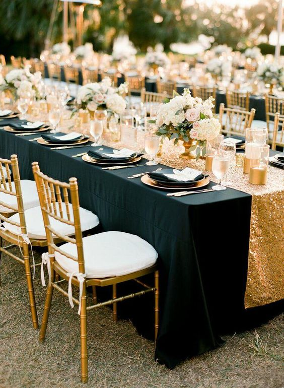 an elegant tablescape with a black tablecloth, a gold sequin table runner, gold vases and candle holders