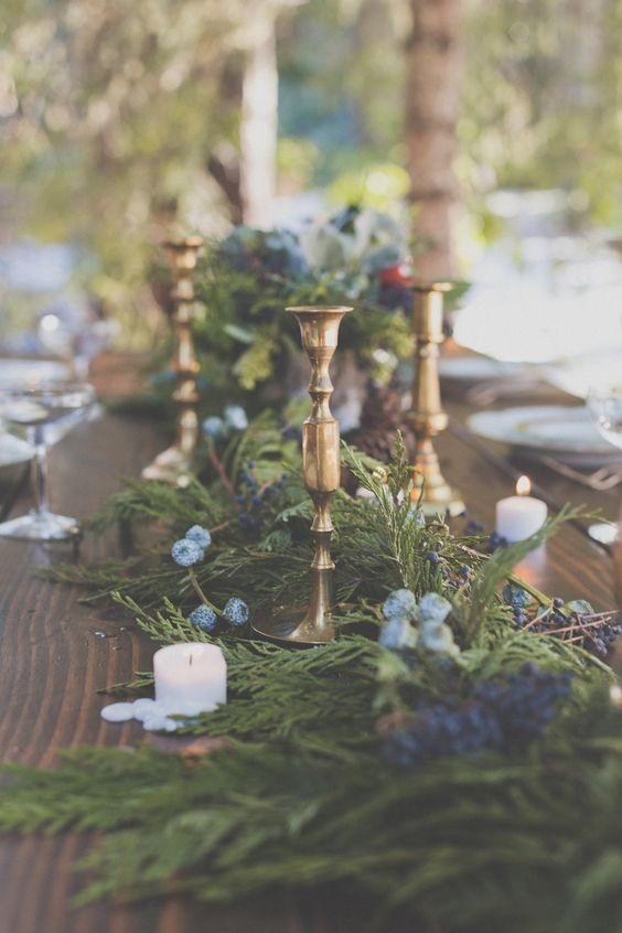 an evergreen table runner with blue flowers and blueberries for a natural feel