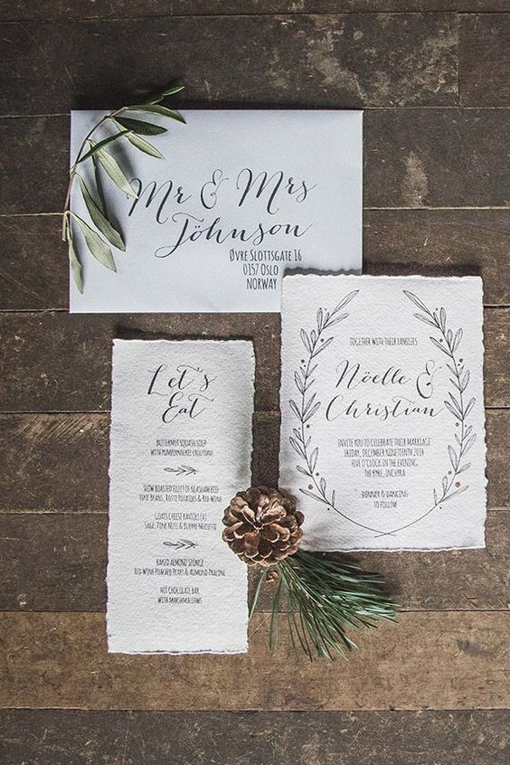 picture of neutral wedding invites with a raw edge and simple black letters for a modern christmas wedding