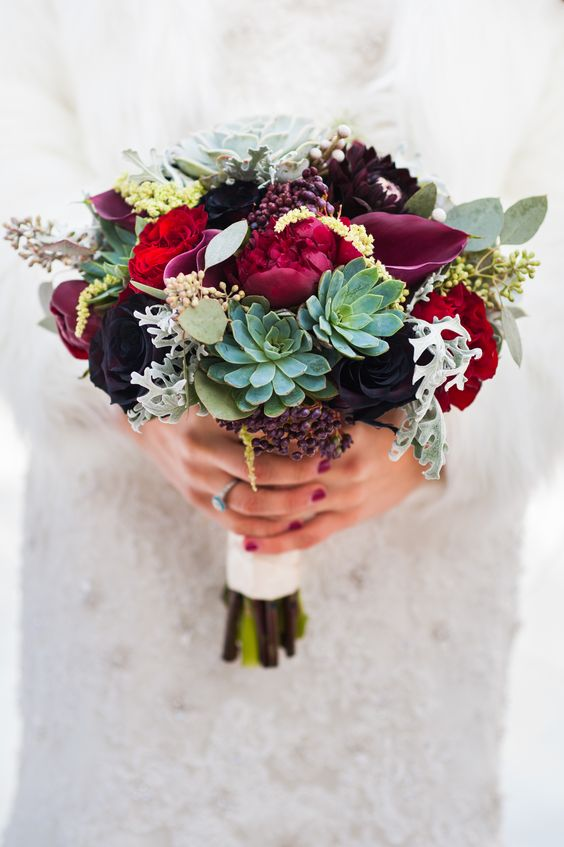 a bold bouquet with privet berries, red and burgundy roses, succulents and pale millet