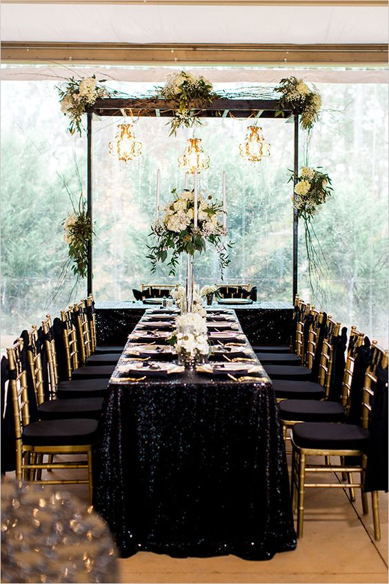 a jaw dropping table setting with gold sequin tablecloth, gold cutlery and candle holders and black and gold chairs
