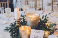 18 a cozy centerpiece with greenery and lots of candle holders