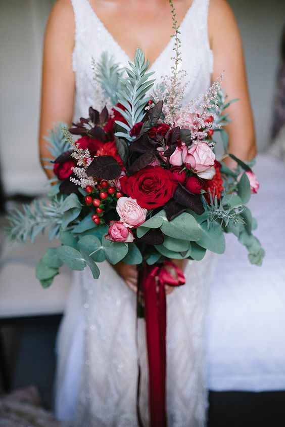 a bold wedding bouquet with dark leaves, red and pink blooms, eucalyptus and other greenery and red ribbons