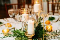 19 a chic greenery centerpiece with threee candles in candle holders and some candles around