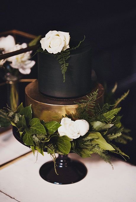 a gold and black wedding cakewith lush greenery and a couple of white flowers