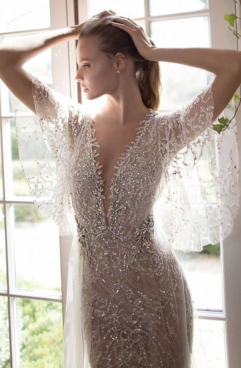 all-sparkling silver wedding gown with wide flowy sleeves and a plunging neckline will make a statement