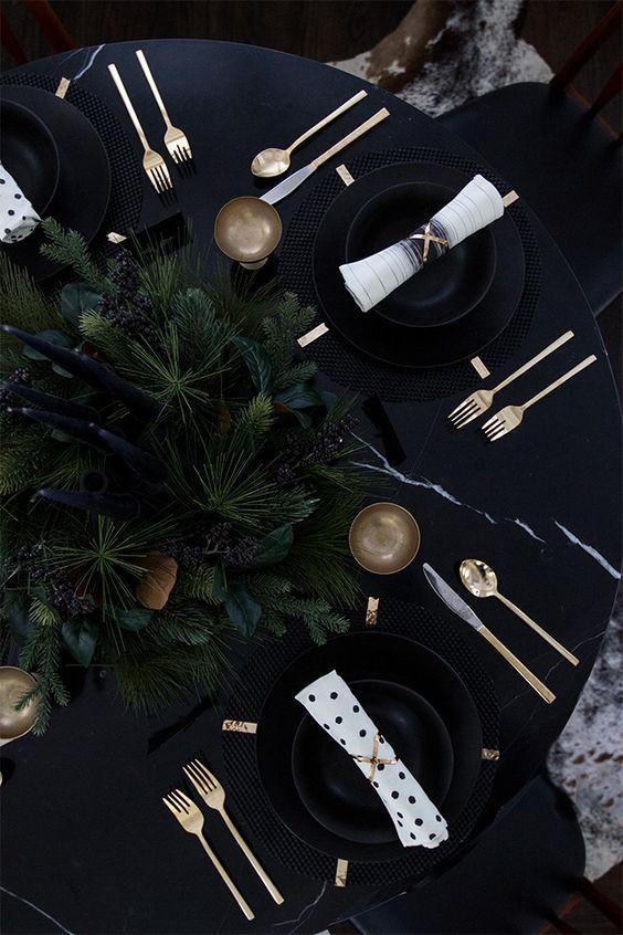 ein stimmungsvolles winter-Einstellung mit schwarzen Platten, gold-Becher, evergreens und schwarze Kerzen