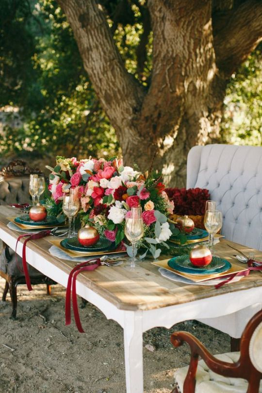 an outdoor winter wedding tablescape with lush pink and white blooms, gilded pomegranates and chargers, vintage upholstered furniture
