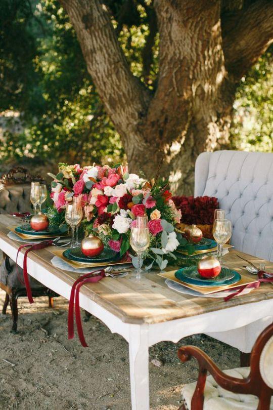 ein outdoor-winter-Hochzeit tablescape mit üppigen rosa und weißen Blüten, vergoldet Granatäpfel und Ladegeräte, vintage-Polstermöbel