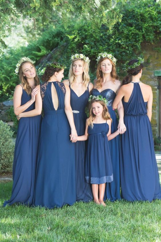 mismatching navy bridesmaids' gowns and a dress for the flower girl