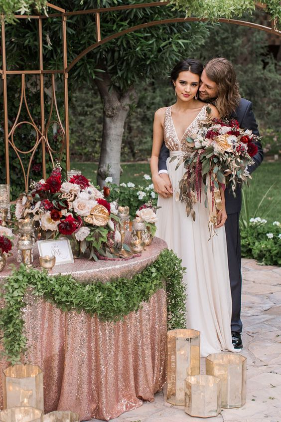 a glam rose gold tablecloth, lush greenery and blooms and candle lanterns for a glam ambience