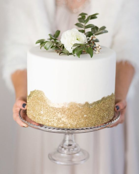 a modern wedding cake with gold glitter and fresh greenery and blooms for an elegant wedding