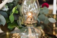 22 a Betty lamp placed on a wooden slice with gilded pinecones looks chic and simple