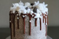 22 a chocolate wedding cake with chocolate dripping, marshmallow snow, edible snowflakes and macarons