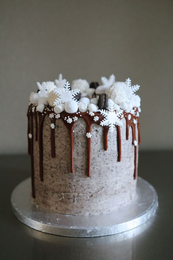 a chocolate wedding cake with chocolate dripping, marshmallow snow, edible snowflakes and macarons