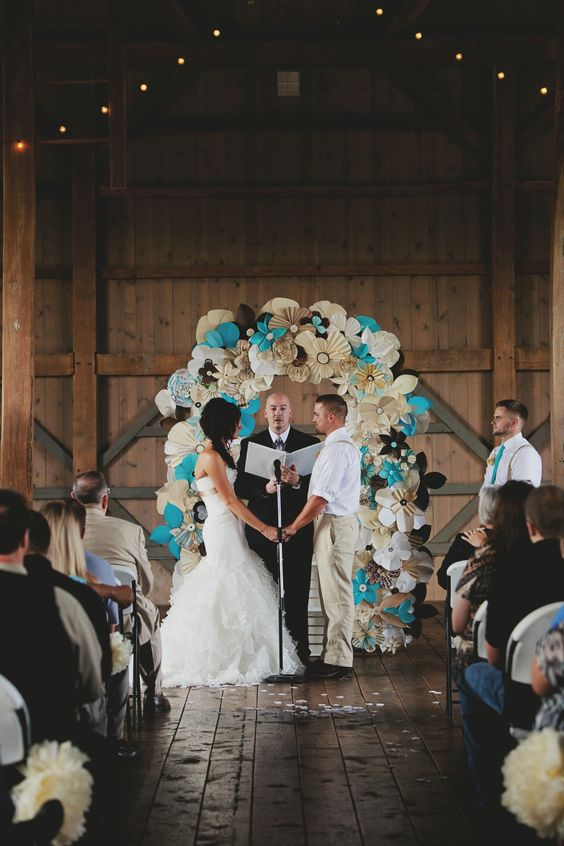 a paper flower wedding arch done in turquoise, ivory and black to fit the wedidng color scheme
