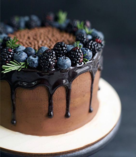 a naked chocolate cake with chocolate drip, blackberries and blueberries and touches of evergreens