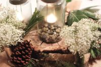 23 a rustic wedding centerpiece with mason jars, pebbles, a wood slice, evergreens, baby's breath