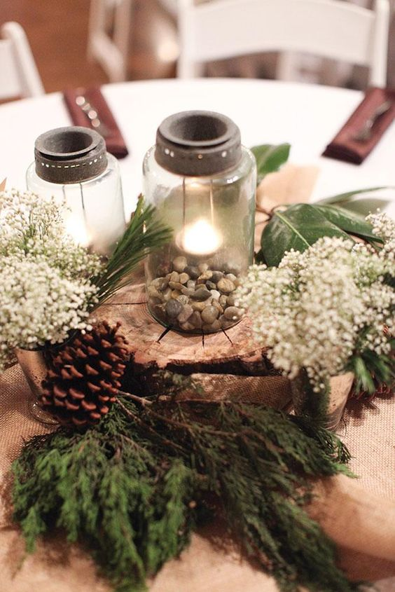 Picture Of a rustic wedding centerpiece with mason jars, pebbles, a ...