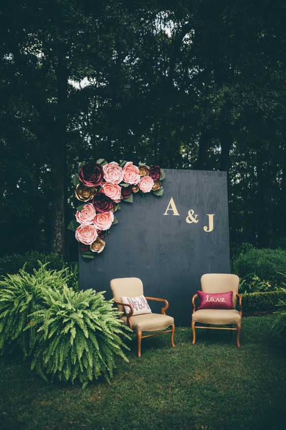 a wedding photo booth with a black wall topped with pink and burgundy flowers and refined chairs