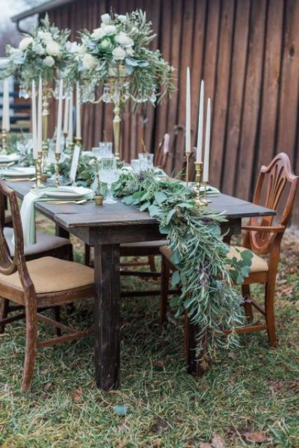 a lush cascading greenery table runner for a rustic winter tablescape and matching centerpieces