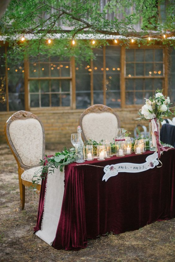 a luxurious sweetheart table with a burgundy velvet tablecloth, a greenery runner and candles