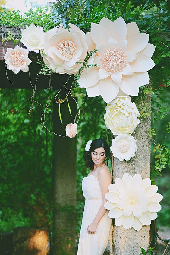 a wedding arbor decorated with oversized blush blooms looks gorgeous