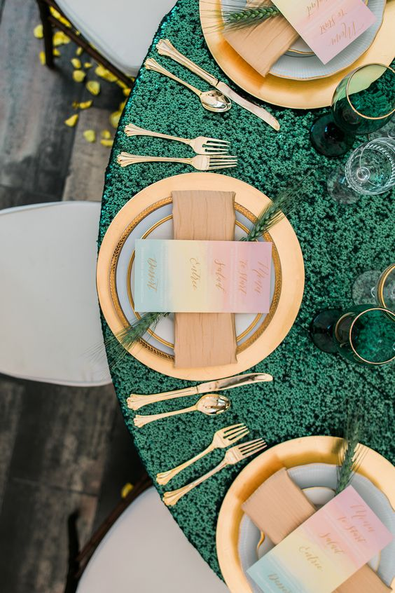 an emerald sequin tablecloth, gold chargers and cutlery, emerald and gold glasses