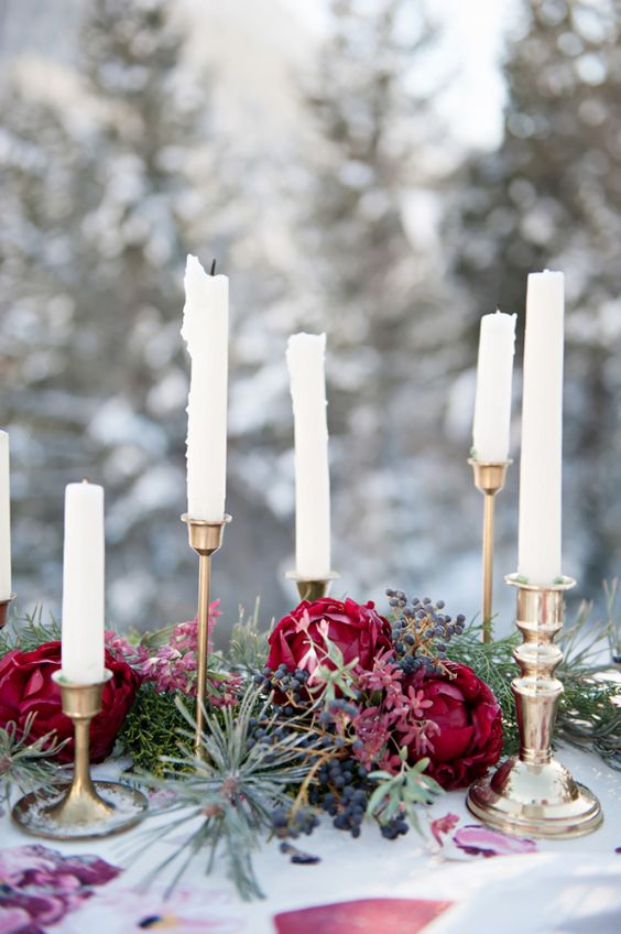 a pine needle and plum-colored bloom garland and candles for wedding table decor