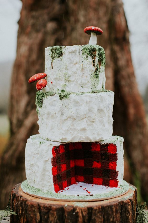 a woodland-inspired lumberjack wedding cake topped with edible moss and mushrooms