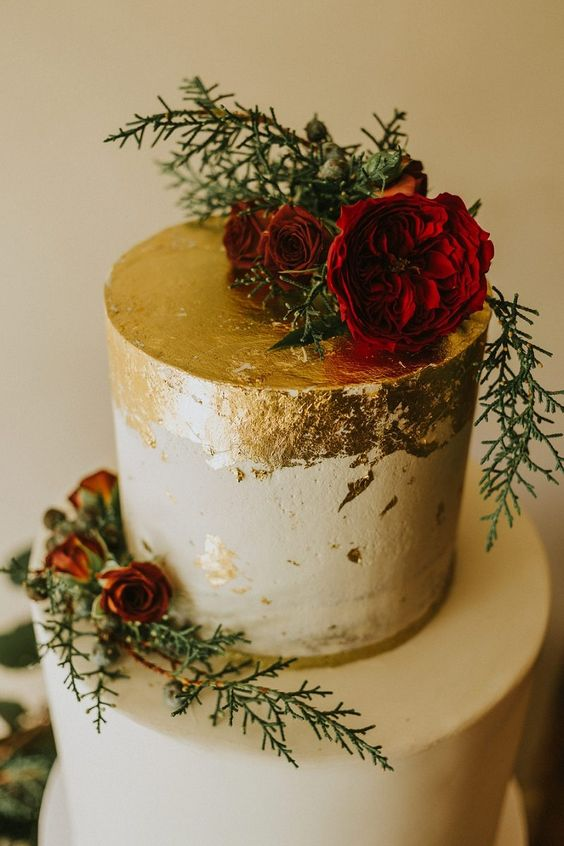 a chic winter wedding cake decorated with gold leaf, evergreens and red roses