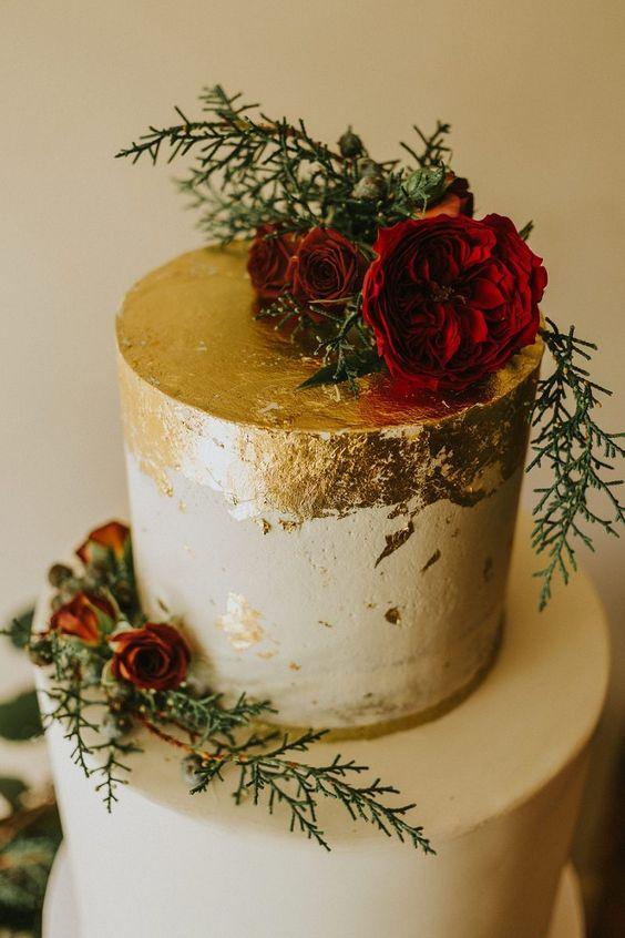 eine schicke winter-Hochzeit-Torte mit Blattgold verziert, evergreens und rote Rosen