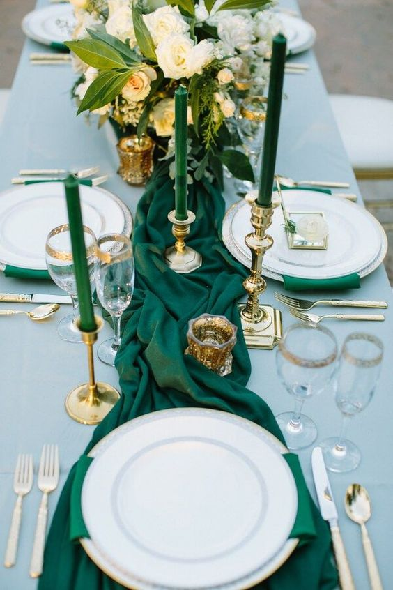 a wedding table setting with emerald candles, napkins and table runners, gold candle holders, glasses and cutlery