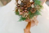26 a woodsy-inspired bouquet with gilded pinecones, ornaments, berries, nuts, fern and a camel ribbon